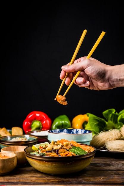 黒の背景に木製の机の上のボウルに麺からエビを取っている人の手のクローズアップ 無料写真