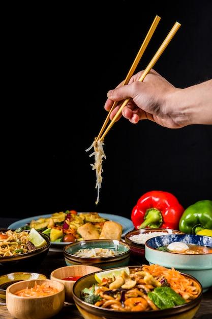 Крупный план руки, используя палочки для еды, чтобы выбрать росток фасоли на черном фоне Бесплатные Фотографии