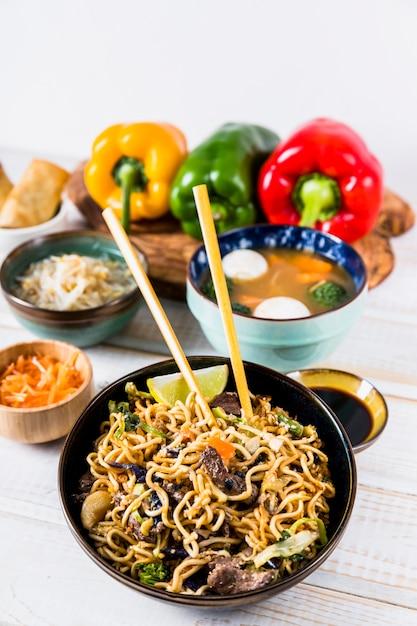 木製の机の上のスープボウルと箸で牛肉のおいしい炒め焼きそば 無料写真