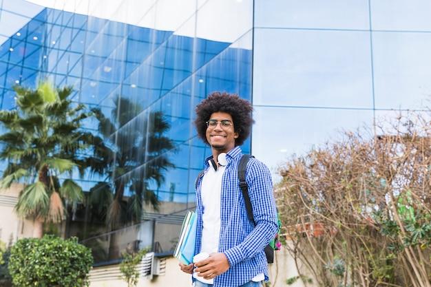 大学の建物の前に立っている男性の若い学生の肖像画 無料写真