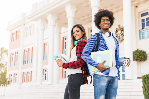本と使い捨てのコーヒーカップ立って大学の建物の前に保持している自信を持って若いカップルの肖像画 無料写真