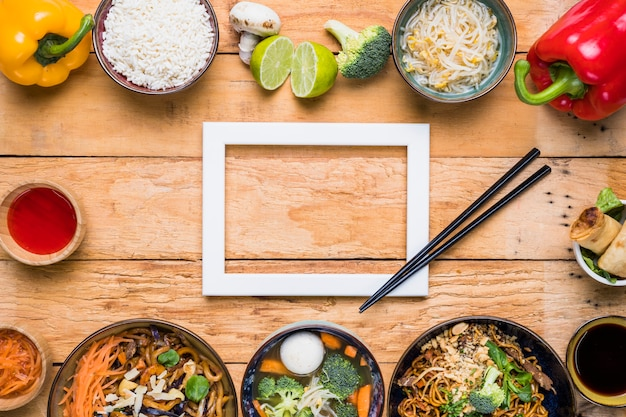 Белая рамка с палочками для еды и тайские традиционные блюда на деревянный стол Бесплатные Фотографии