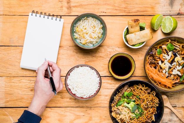 タイの伝統的な料理とスパイラルメモ帳でペンを書く人の俯瞰 無料写真