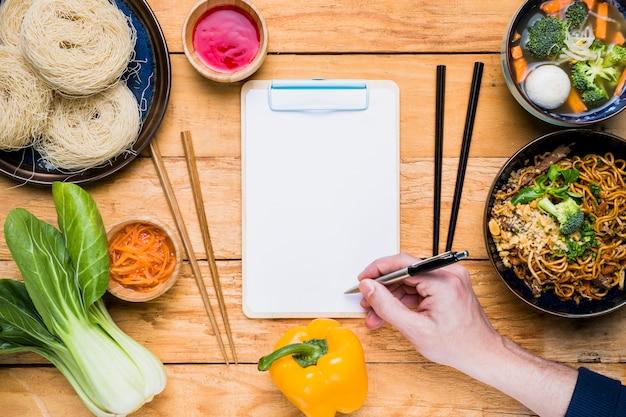 Крупный план руки человека, пишущего в буфере обмена с традиционной тайской едой на деревянном столе Бесплатные Фотографии