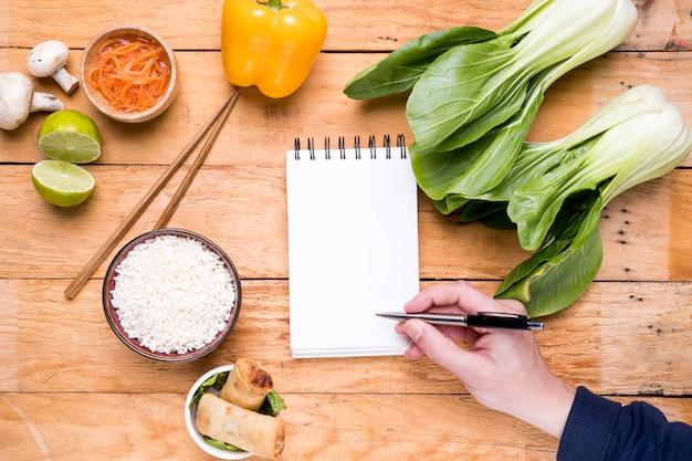 木製のテーブルにタイ料理と空白の白いスパイラルメモ帳に書く人の手のクローズアップ 無料写真