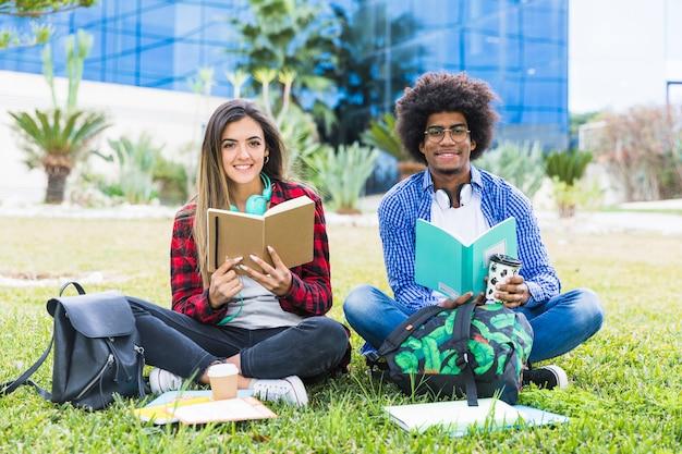 大学のキャンパスで芝生の上に座って本を手で保持している多様な若いカップル 無料写真