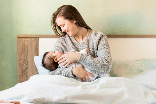 Счастливая мать, держа ребенка на руках в постели Бесплатные Фотографии