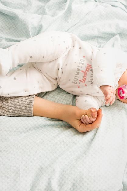 母親と赤ちゃんの軽いベッドの上で手を繋いでいます。 無料写真