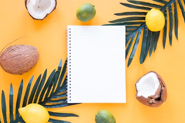 テーブルの上の空白のノートブックとエキゾチックなフルーツ 無料写真