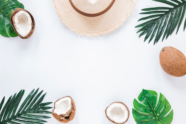 ヤシの葉、ココナッツ、麦わら帽子のフレーム 無料写真