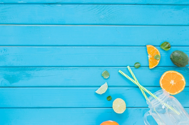 ガラスとストローのテーブルの上の柑橘系の果物 無料写真