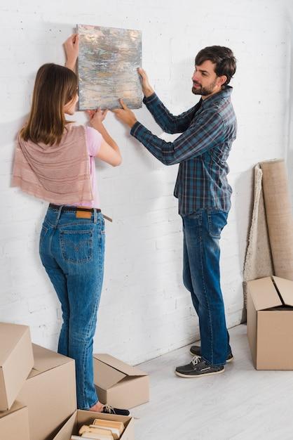 Портрет молодой пары, держащей нарисованную рамку над белой стеной в их новом доме Бесплатные Фотографии