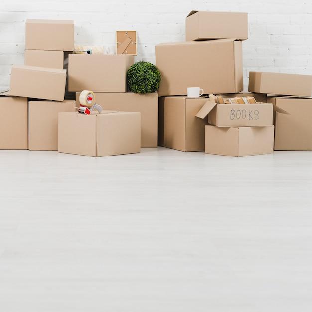 Кружка; завод; клейкая лента и книги на картонных коробках в новом доме Бесплатные Фотографии