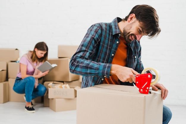 幸せな若い男が段ボール箱と彼女の妻をバックグラウンドで梱包 無料写真