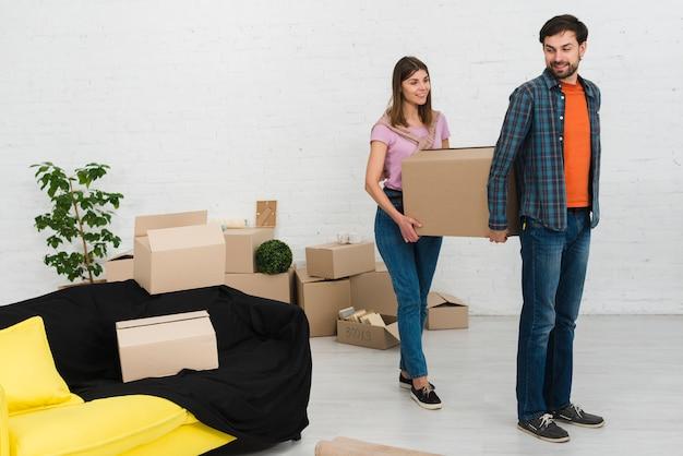 Молодая пара держит картонную коробку в новом доме Бесплатные Фотографии