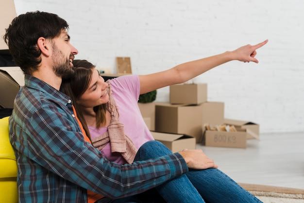 Молодая женщина, показывая ее мужу что-то в их новом доме Бесплатные Фотографии