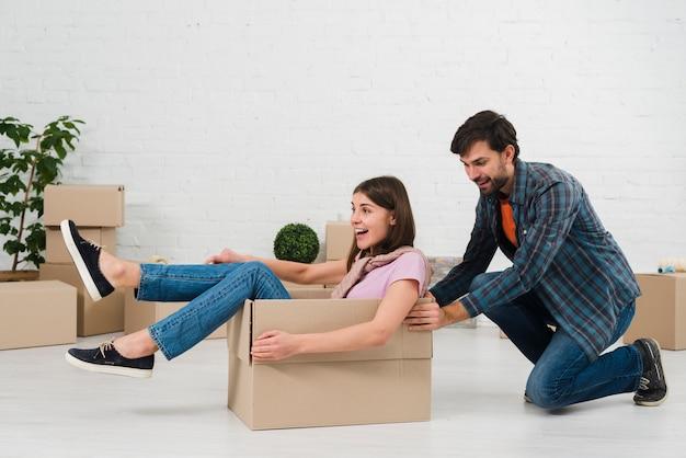段ボール箱に座っている彼の妻を押す夫 無料写真