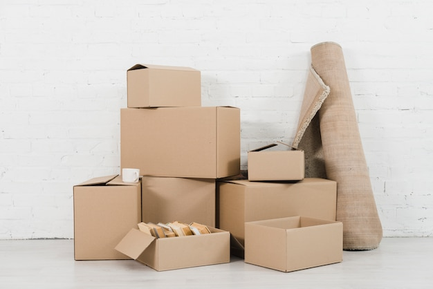 Свернутый ковер с кучей картонных коробок в новой квартире Бесплатные Фотографии