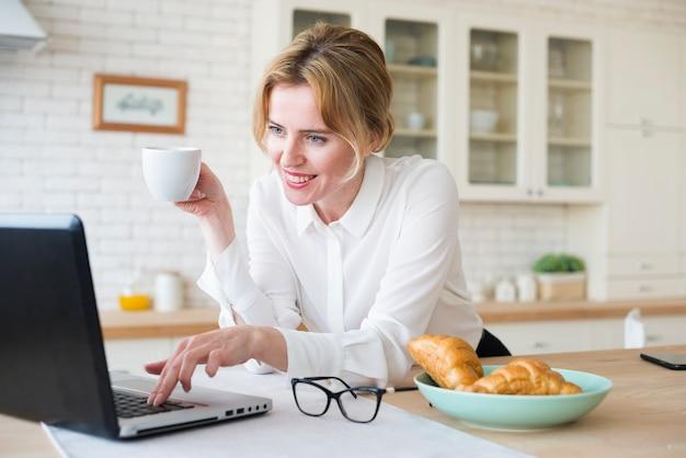ラップトップを使用してコーヒーを飲みながら幸せなビジネス女性 無料写真
