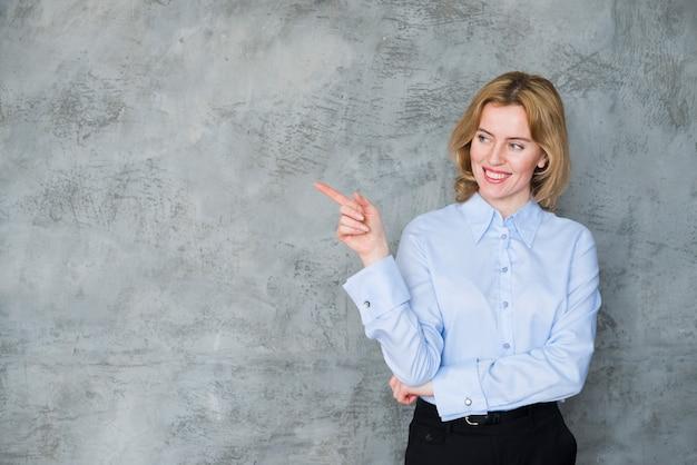 Блондинка деловая женщина, указывая пальцем Бесплатные Фотографии