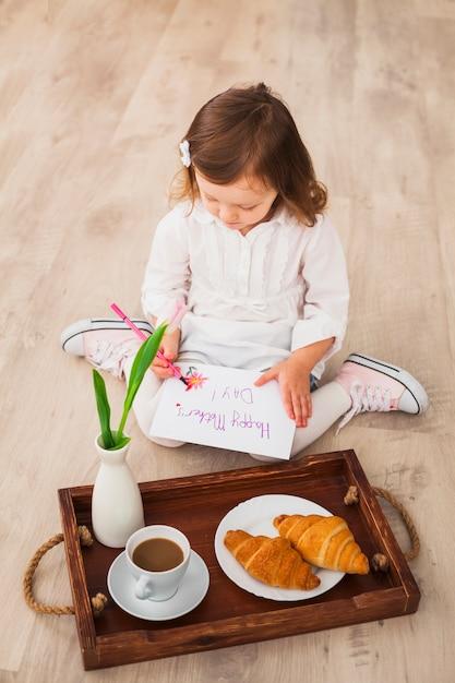 コーヒーとトレイの近く幸せな母の日を書いている女の子 無料写真