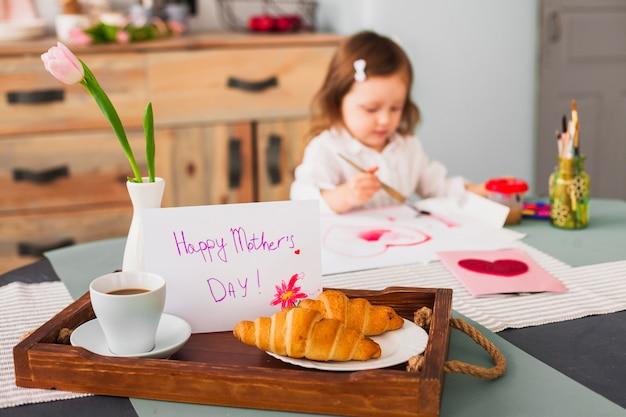 女の子の絵の心の近くのテーブルに幸せな母の日碑文 無料写真