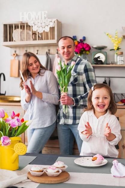 花を持つ親の近くに手をたたく少女 無料写真
