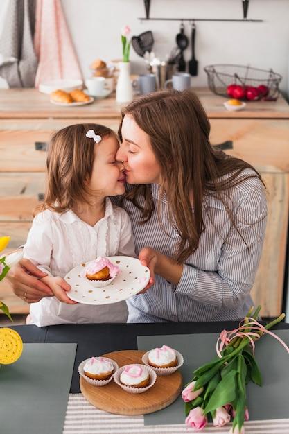 Мать целует дочь с кексом Бесплатные Фотографии
