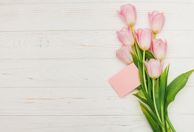 木製のテーブルの上に空のカードとチューリップの花束 無料写真