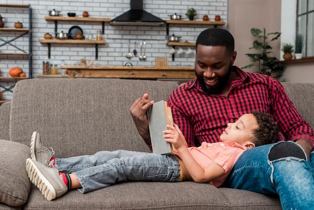 Черный отец и сын читают книгу на диване Бесплатные Фотографии