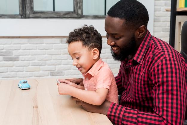 黒の父と息子がタブレットを使用して 無料写真