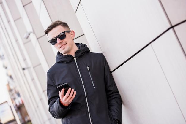 スタイリッシュな若い男が手に携帯電話を保持している壁にもたれて 無料写真