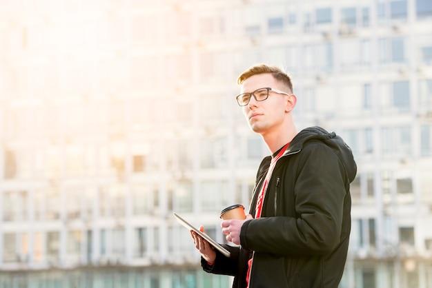 デジタルタブレットとテイクアウトのコーヒーカップを手で押し、ハンサムな若い男の肖像 無料写真