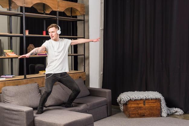 Музыка молодого человека слушая на танцах наушников на софе дома Бесплатные Фотографии