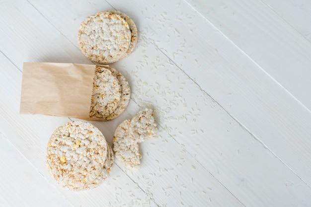 Вид сверху на воздушный рис с зернами на белом деревянном столе Бесплатные Фотографии
