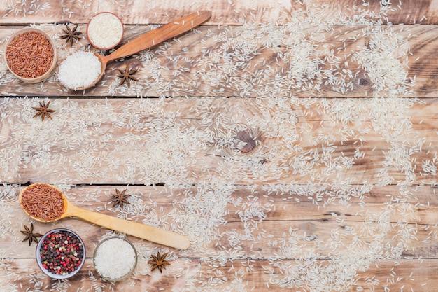 風化した木のテクスチャ背景の上に配置乾燥香辛料と玄米と白米の立面図 無料写真