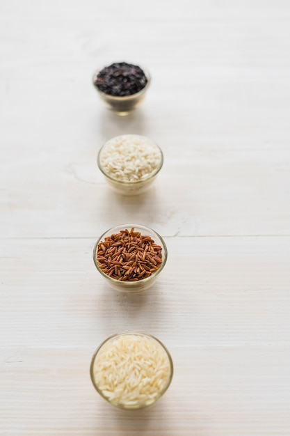 木製のテーブルの上に行に配置されたガラスのボウルに生米の盛り合わせ 無料写真