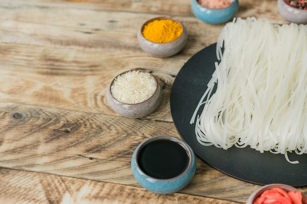 Соевый соус; сырой рис; куркума в миске рядом с сушеной рисовой лапшой на черном подносе на фоне деревянной текстуры Бесплатные Фотографии