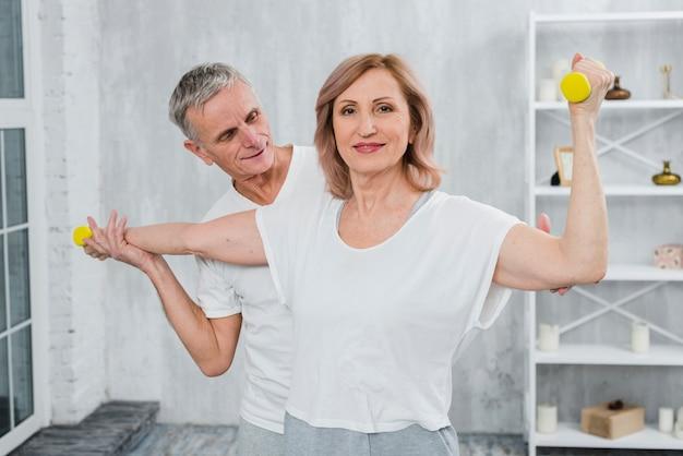 年配のカップルが一緒に自宅でダンベル運動 無料写真