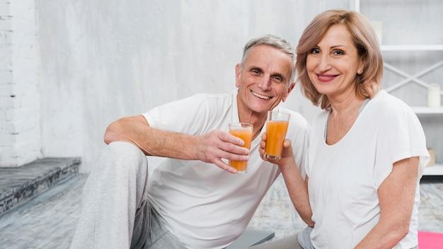 自宅で座って幸せな老夫婦ジュースのガラスを保持 無料写真