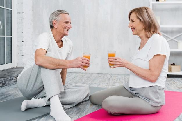 陽気なカップルがヨガをやった後フルーツジュースを楽しむ 無料写真