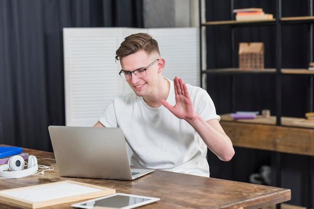 Портрет улыбающегося молодого человека, махнув рукой во время чата на видео на ноутбуке Бесплатные Фотографии