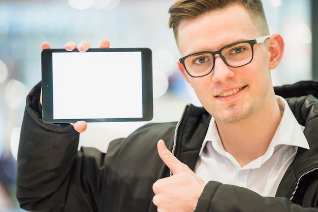 Портрет улыбающегося молодого человека, делая пальца вверх жест, показывая цифровой планшет Бесплатные Фотографии
