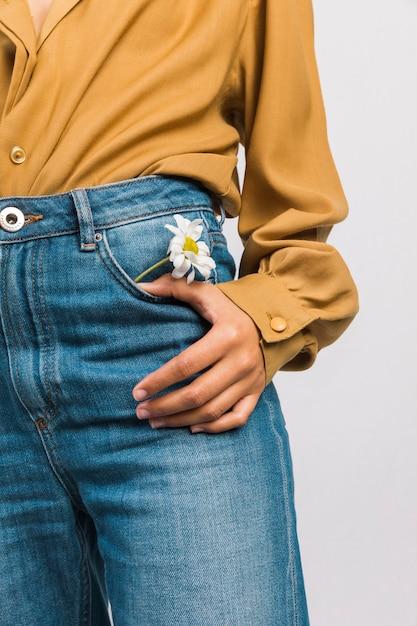 Чернокожая женщина с цветком ромашки в кармане джинсов Бесплатные Фотографии