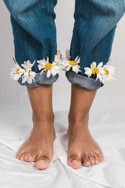 Чернокожая женщина с цветами ромашки в джинсовых манжетах Бесплатные Фотографии