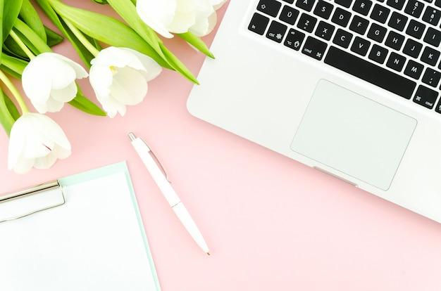 チューリップとテーブルの上のクリップボードとラップトップ 無料写真