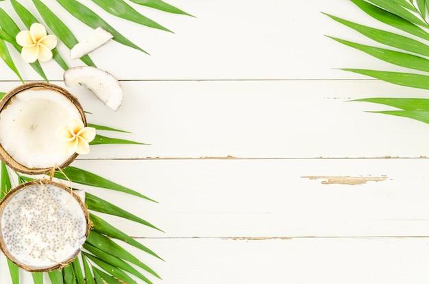 ヤシの葉と木のテーブルにココナッツ 無料写真