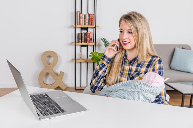 スマートフォンで話す赤ちゃんを持つ女性 無料写真