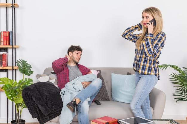 赤ちゃんと父親の近くに電話で話している母 無料写真