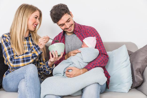 スプーンで赤ちゃんを授乳する両親 無料写真